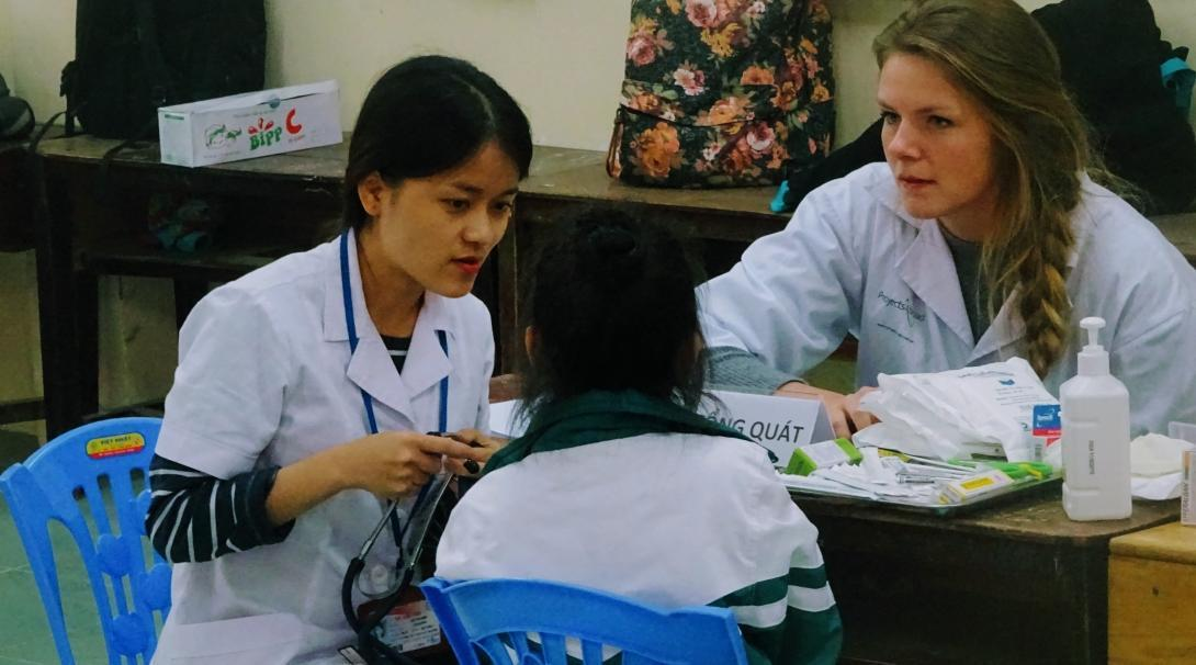 An intern gains dental work experience in Vietnam by helping a local dentist as she works with a patient at an outreach.